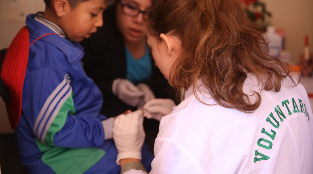 A high school student doing summer medical work experience in Peru checks a child's blood sugar levels.